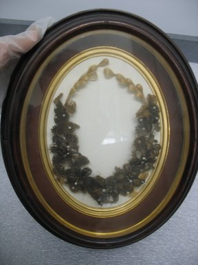 American. Wreath Enclosed in Oval Frame, 1870. Hair, pearls, walnut, 12 1/2 x 10 3/4 x 2 1/8 in. (31.8 x 27.3 x 5.4 cm). Brooklyn Museum, Gift of Peter Taylor Sharp, 45.54.1. Creative Commons-BY