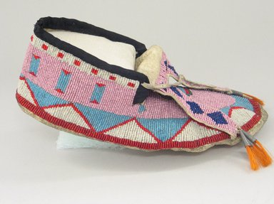 Blackfoot (Native American). Pair of Men's Moccasins, late 19th-early 20th century. Leather, beads, orange horse hair, tin, Each: 10 1/4 x 4 3/4 in. (26 x 12.1 cm). Brooklyn Museum, Charles Stewart Smith Memorial Fund, 46.96.9a-b. Creative Commons-BY