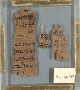 Demotic. Three Small Fragments of Papyrus Inscribed in Demotic', 664-332 B.C.E. Papyrus, ink, Glass: 4 x 4 1/2 in. (10.1 x 11.5 cm). Brooklyn Museum, Bequest of Theodora Wilbour from the collection of her father, Charles Edwin Wilbour, 47.218.147