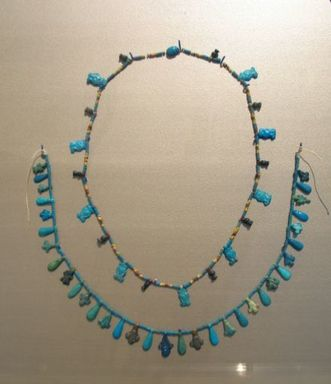 Single Strand Necklace with Hathor Head Beads and a Scarab, ca. 1390-1353 B.C.E. Faience, Length: 8 1/16 in. (20.5 cm). Brooklyn Museum, Gift of Mrs. Lawrence Coolidge and Mrs. Robert Woods Bliss, and the Charles Edwin Wilbour Fund, 48.66.37. Creative Commons-BY