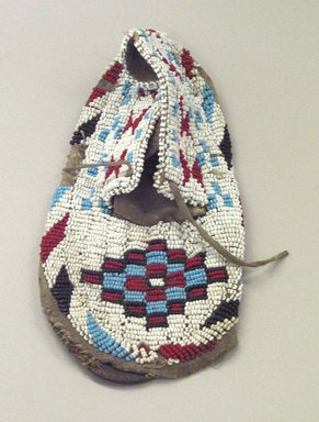 Sioux (Native American). Moccasin with red, white, blue and black geometric beadwork, 1901-1966. Beads, cotton thread, hide, 7 3/4 x 3 1/2 x 3/4 in. or (19.0 cm). Brooklyn Museum, Gift of Mr. and Mrs. Jerome Blum, 66.86.24. Creative Commons-BY