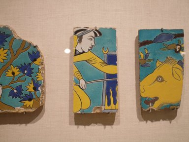 Tile Fragment Depicting a Man Stoking a Fire, first half of the 17th century. Ceramic; fritware, painted in yellow, turquoise, cobalt blue, black, opaque white, and light grayish blue glazes with manganese purple in the cuerda seca (dry-cord) technique, 9 1/4 x 4 3/4 in. (23.5 x 12.1 cm). Brooklyn Museum, Gift of Mr. and Mrs. Charles K. Wilkinson, 71.194.1. Creative Commons-BY
