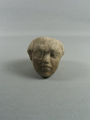 One Head from a Statue of a Prisoner, 750-342 B.C.E. Limestone, 2 5/8 x 2 3/8 x 2 1/2 in. (6.7 x 6.1 x 6.3 cm). Brooklyn Museum, Gift of Miltiades Kyrtsis, 78.190. Creative Commons-BY