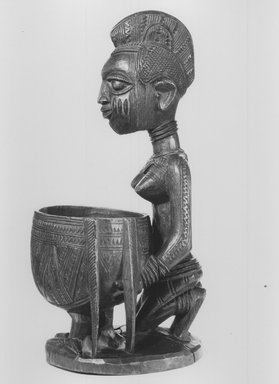 Yoruba. Kneeling Female Figure Holding a Bowl (Agere Ifa), late 19th or early 20th century. Wood, applied materials, (metal & beads in bag), h: 11 3/3 in. (30.0 cm). Brooklyn Museum, Gift of Ann W. Walzer, 80.245. Creative Commons-BY