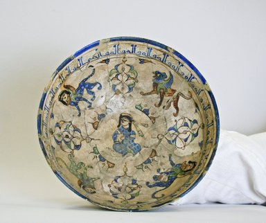 Bowl Depicting a Seated Figure Surrounded by Winged Lions and Sphinxes, late 12th-early 13th century. Ceramic, mina'i (enameled) or haft rangi (seven-colors) ware; fritware, in-glaze painted in blue, green, and brown on an opaque white glaze, overglaze painted in black, 3 1/4 x 7 in. (8.3 x 17.8 cm). Brooklyn Museum, Gift of the Ernest Erickson Foundation, Inc., 86.227.63. Creative Commons-BY