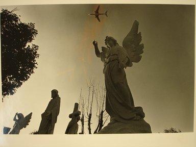 Richard Schiffman (American, born 1952). Untitled (Stone Angel Pointing at Airplane), 1986. Gelatin silver photograph, Image: 8 7/16 x 12 5/16 in. (21.5 x 31.3 cm). Brooklyn Museum, Gift of the artist, 86.54.2. © Richard Schiffman