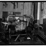 [Untitled] (Two Men Dismantling Metal Frame)