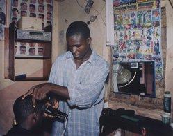 Timothy Feresten (American, born 1954). Haircut, Local Market (Ebonyi State, Nigeria, July 2000), 2001. Dye coupler print, Sheet: 20 x 24 in. (50.8 x 61 cm). Brooklyn Museum, Gift of the artist, 2002.111.2. © artist or artist's estate